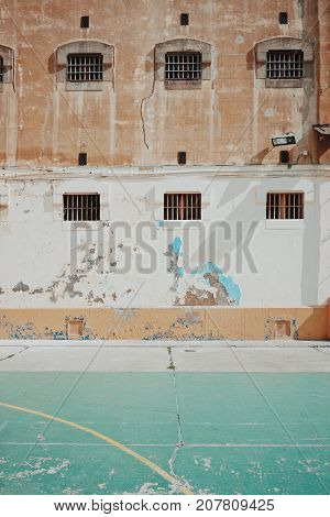 Empty courtyard of old prison with high security little windows with grates and outside playground for prisoners.