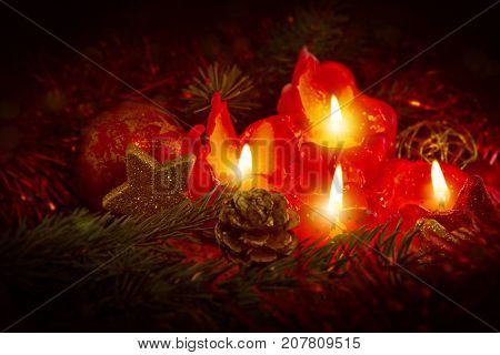 Christmas decoration with christmas bauble and candles for Advent . Four red candles with christmas ball in atmospheric light.