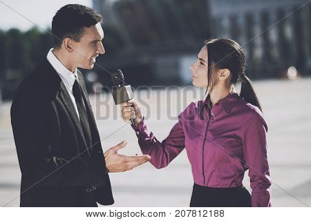 TV reporter at work. A journalist girl in the afternoon interviews a serious man dressed in a black suit.