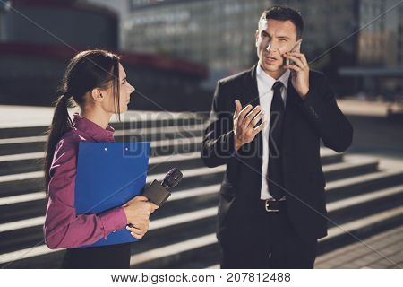 TV reporter at work. Businessman is holding a business conversation on the phone, a girl journalist with a folder stands next to him and looks at him