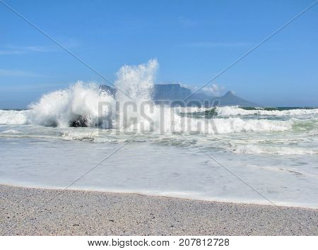WINTER SEASCAPE, WITH HUGE WAVES SMASHING AGAINST SOME ROCKS AND SHOOTING UP INTO THE AIR 01b