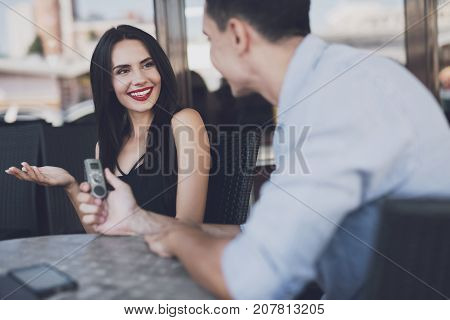 A reporter at work. The woman answers questions with pleasure. The man writes down all the answers to the dictophone. They are sitting at a table in a cafe.