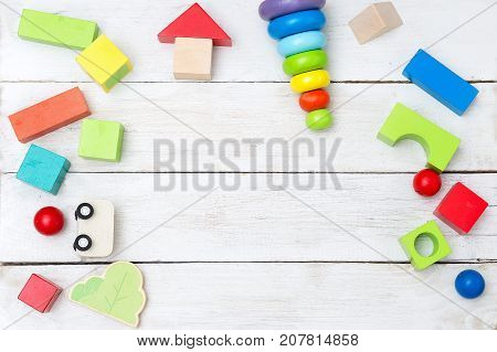 Wooden educational multicolor toys on a wooden background. Copy space