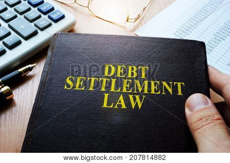 Debt Settlement Law and calculator on a table.