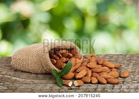 Almonds with leaf in bag from sacking on a wooden table with blurred garden background.
