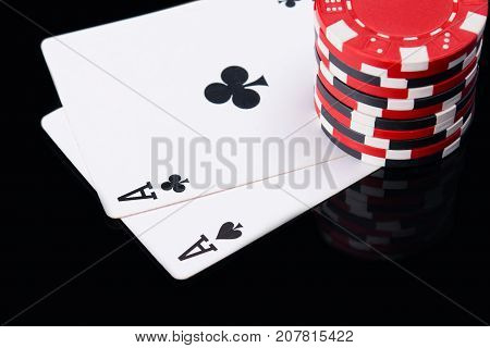high bet of red chips on the game cards on black reflection
