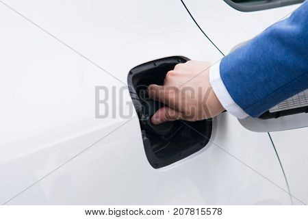 man closes the lid of the gasoline tank of a motor vehicle after refueling with gasoline