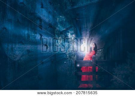 Fantasy photo with a beautiful woman in a red dress at a wooden cottage in a dark forest holding a lantern with rays of light to chase away the bats.