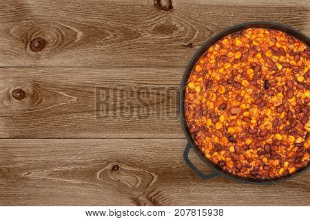 Hot chili con carne in a cast iron pan on dark wooden background top view