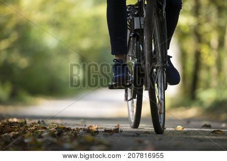 Person riding a bicycle along a fall road with dried autumn leaves scattered on the asphalt in a low angle view of the feet and wheels.