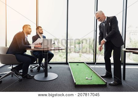 A respectable man in a business suit plays golf in the office. His subordinates sit and watch as he plays