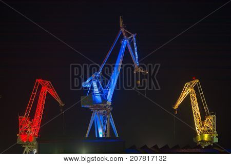 Industrial cargo cranes in the dock at midnight