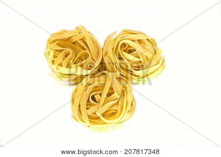Uncooked and raw tagliatelle. Isolate on the white