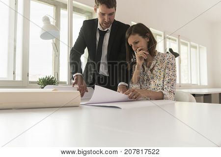 Experienced businessman analyzing important blueprints together with a worried female investor or business expert at desk in the office of a construction company.