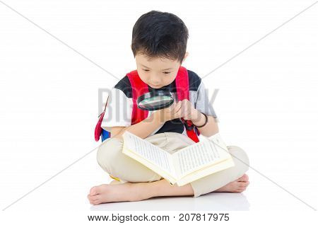 Asian preschool boy with schoolbag magnifying glass and books sitting on the floor
