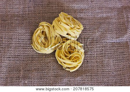 Raw uncooked tagliatelle on the brown sackcloth