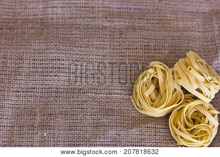 Raw uncııked tagliatelle on the brown sackcloth