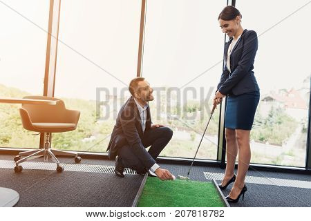 A man in a strict business suit puts a golf ball to strike. Business lady preparing to hit the ball with a golf club