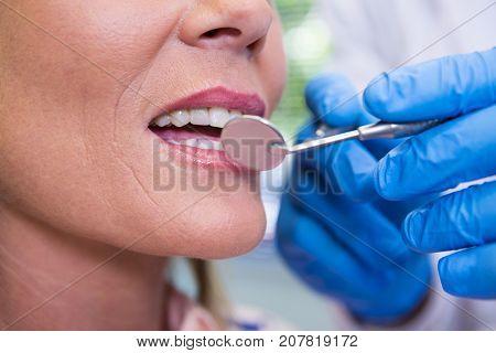Cropped image of dentist examining woman at medical clinic