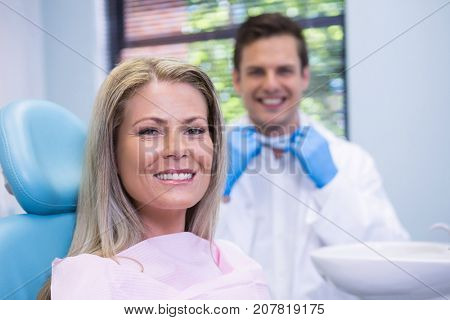 Portrait of smiling woman sitting on chair against dentist at medical clinic