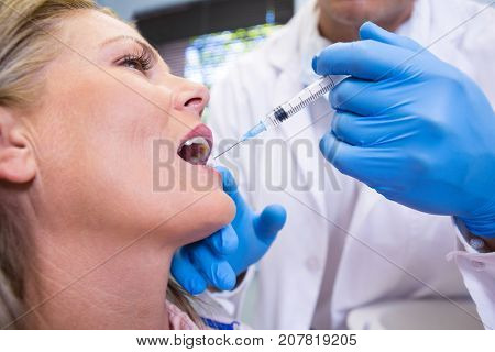 Close up of dentist holding syringe by patient at medical clinic