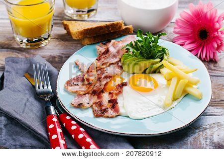 Continental breakfast with fried eggs, bacon and drinks. Ketogenic diet concept. Space for text