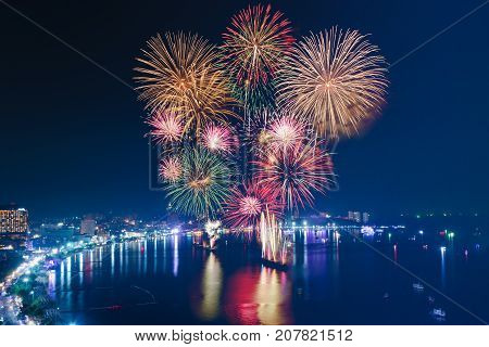 Colourful Fireworks over the sea beach with blue twilight sky background and city view