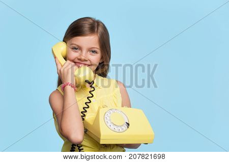 Little model smiling at camera while holding obsolete telephone and looking at camera.