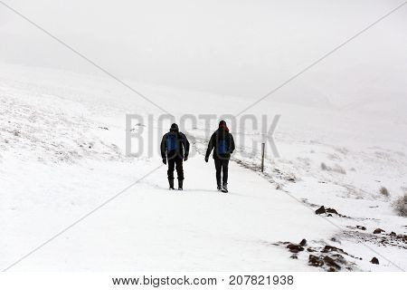Two unrecognizable men are walking down the snow covered mountain of Pen y Fan Mountain in the Brecon Beacons National Park with poor visibility and dangerous climbing conditions.