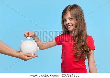 Charming little girl smiling at camera while putting coin in piggybank on blue background.