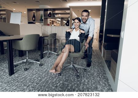 Man and woman in the office. A man is rolling a woman in an office chair. She took off her shoes and held them in her hands. They are having fun