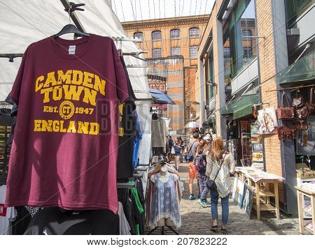 London, UK: July 26, 2016: Shoppers walk through the stalls in the open air Camden Lock Market in London.