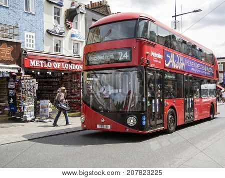 London, UK: July 26, 2016: Tourists and shoppers walk in Camden Town, London's most popular open-air market area with stalls, shops, pubs and restaurants. The number 24 bus drives past.