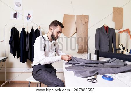 Side view portrait of handsome young man sewing bespoke suit at table in traditional atelier studio