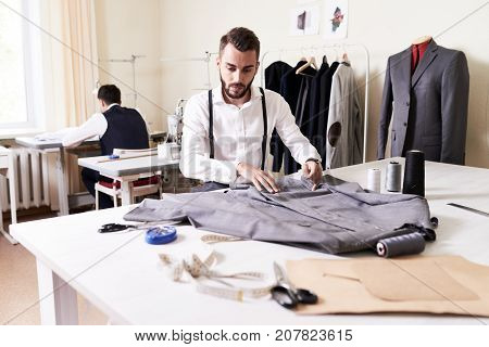 Portrait of handsome tailor working in atelier studio sewing suit jacket at table