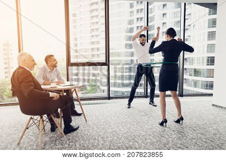 Fun in the office. A man and a woman twist hula hoops. Two of their colleagues sit at the table and look at them. On the background of a large panoramic window overlooking the business center