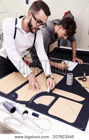 Portrait of two young tailors working in atelier studio, making patterns for clothes and sketching at table with different tools
