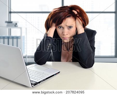 young sad and frustrated business woman working in stress at modern office window room pulling her hair tired and suffering depression in job problems and excess work load concept