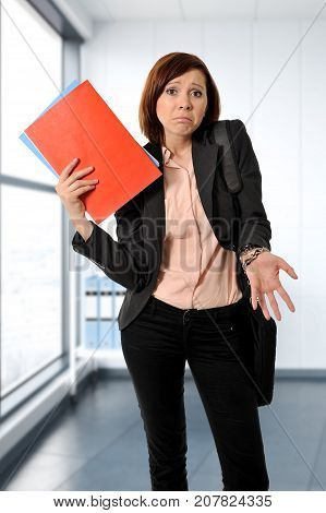 business red hair woman or student in stress thinking worried while carrying a portfolio notepads and wearing suit at modern office room looking frustrated and stressed