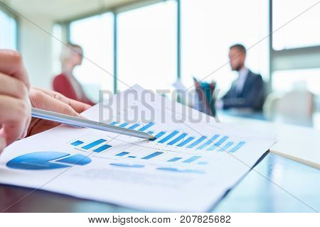 Closeup of unrecognizable business person  pointing to statistics graph analyzing marketing data  with other people in background, copy space
