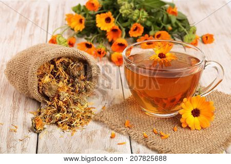 Calendula tea with fresh and dried flowers on white wooden background.