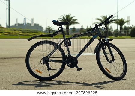 mountain bike stands on the asphalt against the background of a blurry city landscape