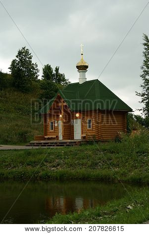 a small modern building of the Orthodox baptistery made in the traditional style of wooden architecture standing near the lake