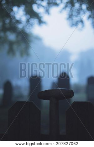 Handle Of Spade Against Fence Of Cemetery In Mist.