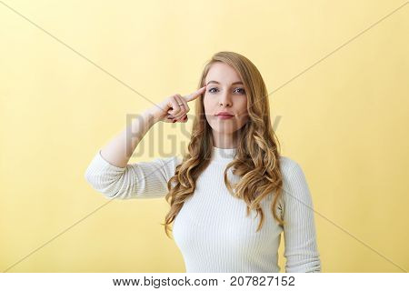 Use your brain. Stop talking nonsense. Irritated female teacher twisting finger at temple having arrogant look during maths class annoyed with her clueless and foolish students. Body language