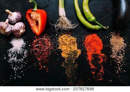 food spice salt mustard pepper paprika tumeric garlic pepper eggplant scallion dark background concept