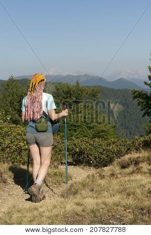 a girl with poles for nordic walking flask for water and and a camera bag walking along a mountain path against the backdrop of the mountain peaks in the background
