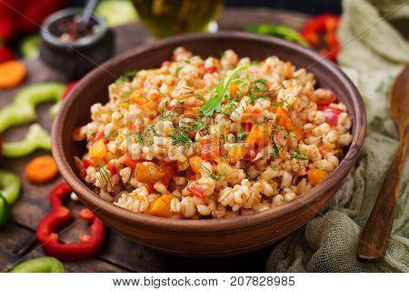 Vegetarian Crumbly Pearl Barley Porridge With Vegetables  In A Dark Background