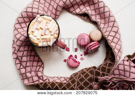 Concept of cold winter morning with latte and macaroons. Hot drink with marshmallow and colorful sweets nearby with checked scarf around, top view