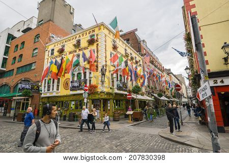 DUBLIN IRELAND - AUGUST 10 2017; Tourists wander the streets of Temple Bar area passing yellow building Gogarty's bar a popular travel destination with quaint old buildings bars and shops.